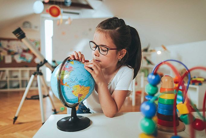 Young girl in glasses examining a globe.