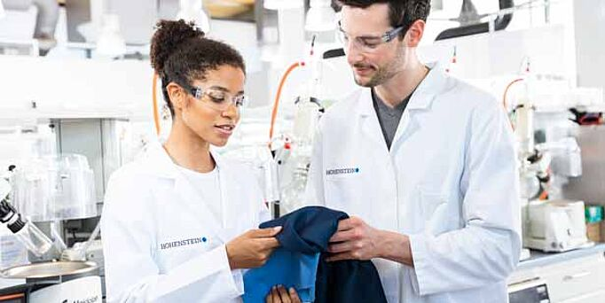 Two Hohenstein lab employees holding a piece of blue fabric