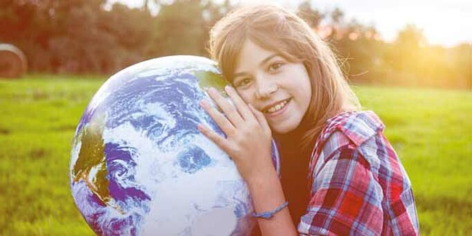 Young girl holding a globe.